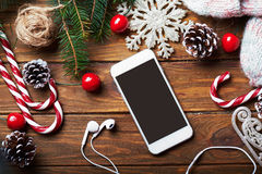 Smart phone mock up with rustic Christmas decorations. Stock Photos