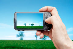 Smart phone in nature landscape Royalty Free Stock Photography