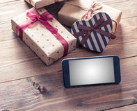 Smart phone near gift boxes. Clipping path included. Royalty Free Stock Photo