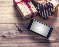 Smart phone near gift boxes. Clipping path included. Stock Photography