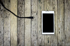 Smart phone need to charge a battery on wood plank Stock Photography