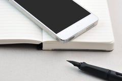 Smart phone, notebook, and pen Stock Photos