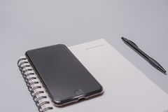 Smart phone, notebook and pen on the office table on white background. Business concept. Smart phone, notebook and pen on the office table on white background Royalty Free Stock Images