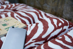 Smart phone and a notebook place on a hug pillow Royalty Free Stock Photography