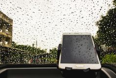 Smart phone is off line with raindrops background, Working on the rainy day in the car. Telephone or smartphone with raindrops background on the mirror in front Stock Photo