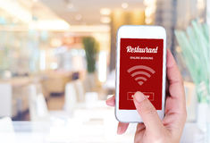 Smart phone with online booking on screen over blur restaurant b Stock Photography