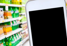 Smart phone over blur product shelves in supermarket background Royalty Free Stock Photography