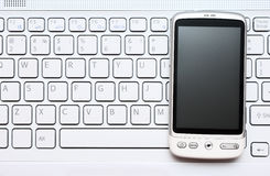 Smart phone over white keyboard Royalty Free Stock Photos
