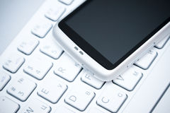 Smart phone over white keyboard Royalty Free Stock Image