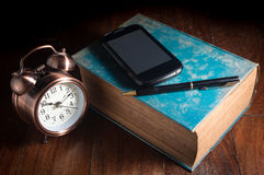 Smart phone and pen on antique book with alarm clock. Royalty Free Stock Photo