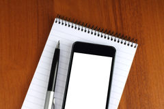 Smart phone, pen and notepad Royalty Free Stock Image