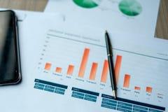 Smart Phone, penna, rapporto finanziario, computer con il grafico del grafico fotografia stock
