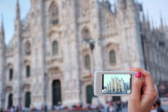 Smart phone photography. Girl hand holding smart phone and taking pictures of Milan cathedral Royalty Free Stock Photography