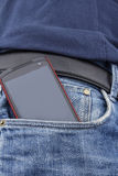Smart phone in a pocket. Red smart phone in the front pocket of a pair of blue jeans Stock Photography