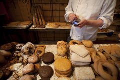 Smart Phone in Retail. A bakery owner checked his store supplies on a smart phone Stock Images