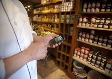 Smart Phone in Retail. A bakery, grocery store owner checked his store supplies on a smart phone Stock Image