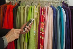 Smart phone in retail. A person checks clothing inventory at store with a smart phone Stock Photography