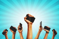 Smart phone Revolution. Group of people`s hands holding phones and rising them up agains a shiny background celebrating the smart revolution royalty free stock photos