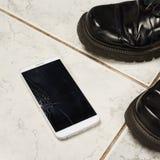 Smart Phone rotto sopra le mattonelle Immagini Stock Libere da Diritti