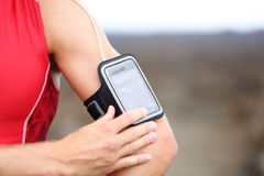 Smart phone running music closeup - male runner. Listening to music adjusting settings on armband for smartphone. Fit man fitness model working out outside in Royalty Free Stock Images