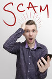 Smart phone scams concept, shocked guy with open mouth. Holding smart phone in his hand. Graphic handwritten word Scam in background Royalty Free Stock Photos