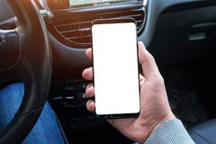 Smart phone with  screen for mockup in car driver hand. Close up. Steering wheel and car interior in background Royalty Free Stock Image