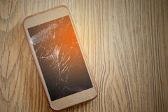 Smart phone screens cracked down. On the wooden floor Stock Photography