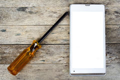 Smart phone and screwdriver for repair on wood plank Royalty Free Stock Photography