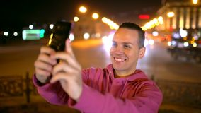 Smart phone selfie - attractive hispanic man taking self portrait using smartphone camera. Young man taking selfie in