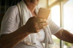 Smart Phone senior della tenuta della mano della donna in palestra Workou Fotografie Stock