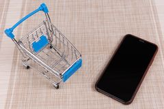 Smart phone and shopping cart on pattern background
