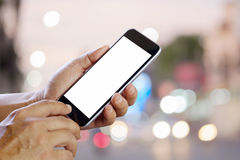 Smart phone showing blank screen in business man hand at walk st. Reet night light bokeh Background Stock Photos