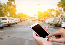 Smart phone showing blank screen in man hand with blur cars park Stock Photos