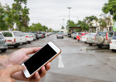 Smart phone showing blank screen in man hand with blur cars parking. Royalty Free Stock Photos