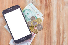 Smart phone and singapore dollar on wooden table Stock Photography