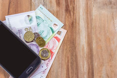 Smart phone and singapore dollar on wooden table Stock Photo