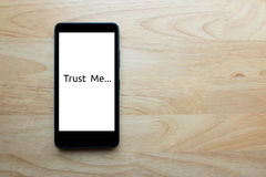 Smart phone slaves. Smart phone show text on screen `trust me` status show today, human is the slave of technology too on wooden table background Stock Photos