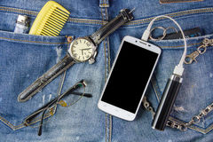 Smart phone, Spectacles, portable battery and watch on jeans bac. Kground Royalty Free Stock Photos