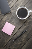 Smart phone with sticky note paper and cup of coffee. On old wooden desk royalty free stock image