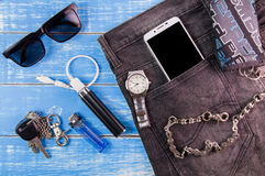 Smart phone, sunglasses, portable battery, jeans, wallet and wat. Ch on blue wooden  background Royalty Free Stock Photo