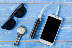 Smart phone, sunglasses, portable battery and watch on blue wood Royalty Free Stock Photos