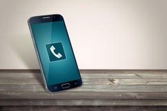 Smart phone on table calling. Mockup Royalty Free Stock Image