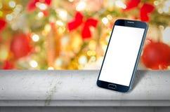 Smart phone on table christmas tree. Smart phone on table front of a christmas tree Stock Photos