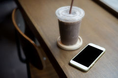 Smart phone on the table with oce coffee inside coffee shop Royalty Free Stock Photo