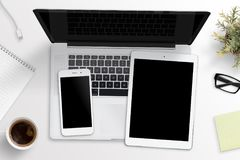 Smart phone and tablet mockup on laptop keyboard. Office desk concept Royalty Free Stock Photography