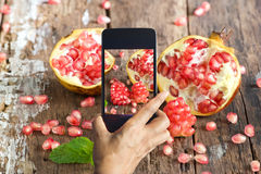 Smart phone take photos of pomegranate on wooden background Royalty Free Stock Images