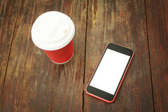 Smart phone and takeaway coffee cup on wooden table Royalty Free Stock Images