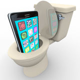 Smart Phone in Toilet Frustrated Old Model Obsolete. A smart phone with apps being flushed down a toilet symbolizing frustration with poor service, outdated and Royalty Free Stock Photo