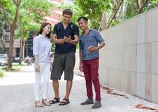 Smart Phone turistico delle cellule di aiuto asiatico delle coppie Immagini Stock