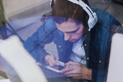 Smart phone user. Man using smart device with headphones stock photo